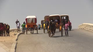 People in horse drawn carts down a street, Public Transport, Tourists at the Great Pyramid of Giza riding in horse drawn carts, carriages, karts, Cairo, Egypt, Africa