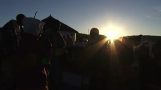 Silhouette of people dancing at traditional dance carrying sticks in Lesotho highlands at sunset/sunrise, dawn/dusk, Rural Lesotho, Africa