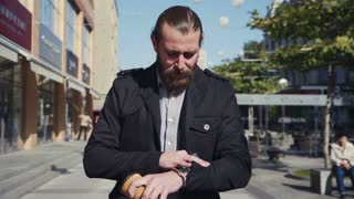 4K Businessman with beard walking down the street with cup of coffee, using smartphone and watch