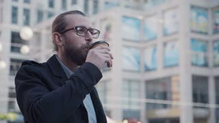 4K Close up of man with beard, ponytail and glasses standing on city street, drinking takeaway coffee looking around and smiling