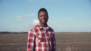 4K handsome smiling black man wearing plaid shirt stands beside plowed field