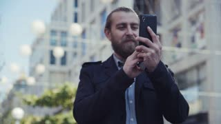 4K Low angle view of man checking his phone reception while standing in city by tall office building