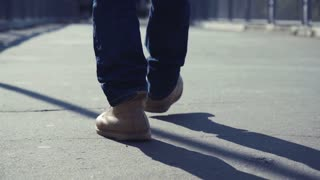 4K Low angle view of the feet of a male legs in yellow boots going through urban environment