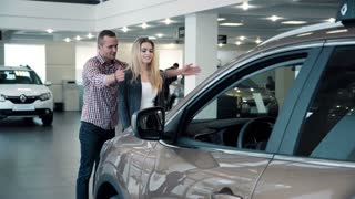 4K Man surprises wife or girlfriend in car dealership, showing new car
