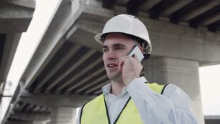 4K movement stabilized shot of handsome caucasian worker in white helmet and yellow vest talking on mobile phone while standing under overpass construction