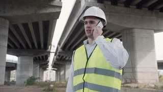 4K shot of handsome caucasian worker in white helmet and yellow vest talking on mobile phone while standing under overpass construction