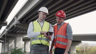 4K shot of Two young workers in red and yellow vests and hard hats lookig at tablet computer and discusses a project while standing under the bridge construction. Movement stabilized