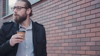 4K Stylish businessman with beard, in glasses and black jacket walking along brick wall and drinking coffee on day in city