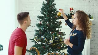 A couple decorate a Christmas tree