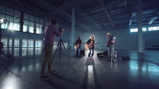 A director aiming with the camera to the band performing a song while video making. Camera movement around