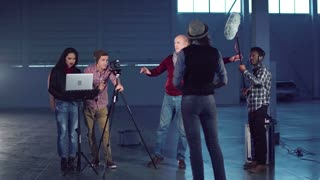 A group of people shooting a video blog in a studio hangar