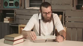 Adult bearded man in glasses reading book at table and looking at camera