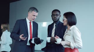 Adult businessman explaining aspects of using vr headset while people drinking from cups