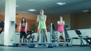 Aerobics class doing jumps on steps together