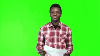 African man in a plaid shirt holds up a Thank You sign and smiles at the camera