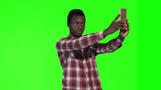 African young man make selfie using smartphone on green screen