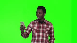 African young man make video call using smartphone on green screen background