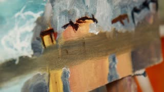 Artist applying a brush stroke to a canvas with an old paint bespattered paintbrush in a close up detail view