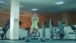 Athlete female doing squats and jumps on fitness step