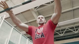 Athlete in red t-shirt lift does exercise workout with bar in gym