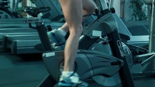 Athletic female pedaling on the simulator on a stationary bike at the gym.