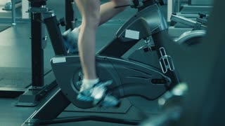 Athletic female with headphones pedaling on the simulator on a stationary bike at the gym.