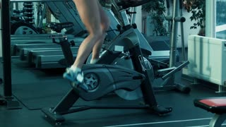 Athletic woman pedaling on the simulator on a stationary bike at the gym.