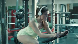 Athletic woman with headphones pedaling on the simulator on a stationary bike at the gym.