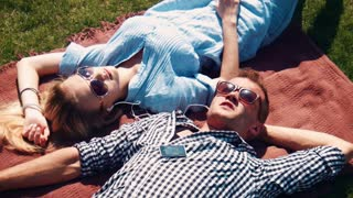 Attractive young couple relaxing in the summer sun lying on their backs on a rug outdoors on the grass head to head with the young man listening to music