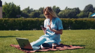 Attractive young woman put her mobile phone into the VR headset and start to watch or play game or video in park on the lawn