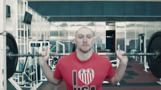 Bald athlete with beard in red t-shirt lift heavy weight bar in gym on exercise machine and looking straight to the camera. Tired after workout