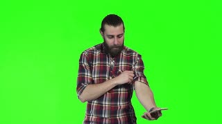 Bearded caucasian young man make selfie using smartphone on green screen