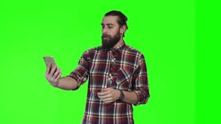 Bearded caucasian young man make video call using smartphone on green screen background