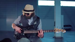 Bearded man in sunglasses and hat wearing vest and shirt sitting on chair, playing black electric guitar and smiling in empty hall with studio lighting. Camera moving around