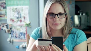 Beautiful blonde adult caucasian woman sitting at home in kitchen with stylish eyeglasses with smartphone and credit card shopping online in internet using app on cell phone. She happy to buy purchase