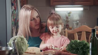 Beautiful mother and daughter in kitchen. Girl cuts, chop cheese then feeding mother with it