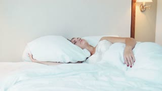 Beautiful young adult woman in nightgown sleeping in bed with large pillows in hotel room. Includes copy space