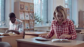 Blonde girl student in checked shirt working in classroom with book and tablet, flipping pages and making notes