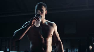 Bodybuilder with a muscular physique drinking water after working out in a darkened gym , with copy space alongside, close up upper body frontal