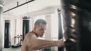Boxer hitting the punching bag in gym