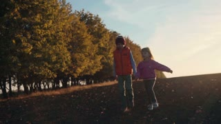 Boy and girl walking in front camera at sunset. Autumn landscape