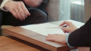 Business male and female in official suits sign paper