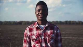 Cheerful african guy in plaid shirt standing in field with arms crossed and looking at camera