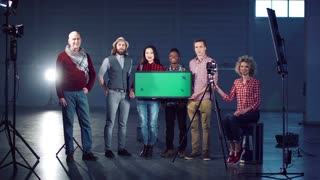 Cheerful film diverse team posing with a chromakey board