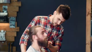 Client showing how to cut his beard to barber