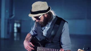Close 4K shot of bearded man in sunglasses and hat playing the bass guitar sitting in smoke while video production process. Camera moving around