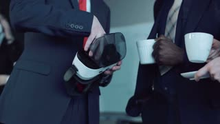 Close shot of hands of businessman holding vr headset explaining aspects of vr headset while people drinking from cups