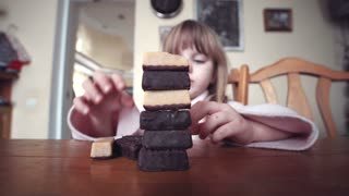 Close shot of the little girl builds a tower of chocolates of bricks and smiles. Then the tower falls and she is angry