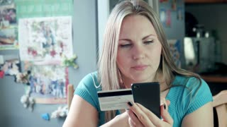 Close-up of blonde adult woman sitting at home in the kitchen make shopping online on the internet using smartphone and credit debit electron card
