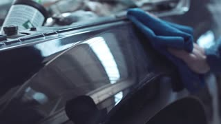 Close up of person polishing black car in workshop